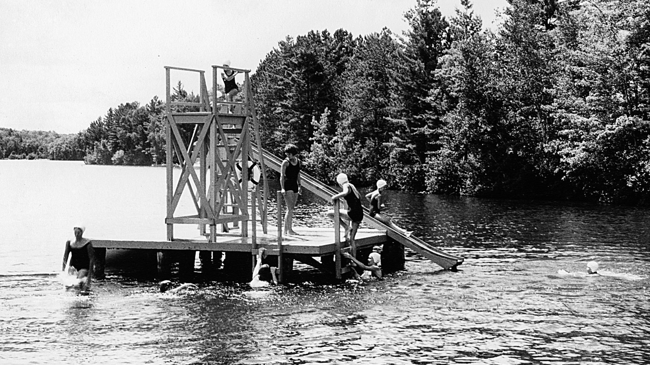 Black and white photo of 1965 campers on camp diving platform