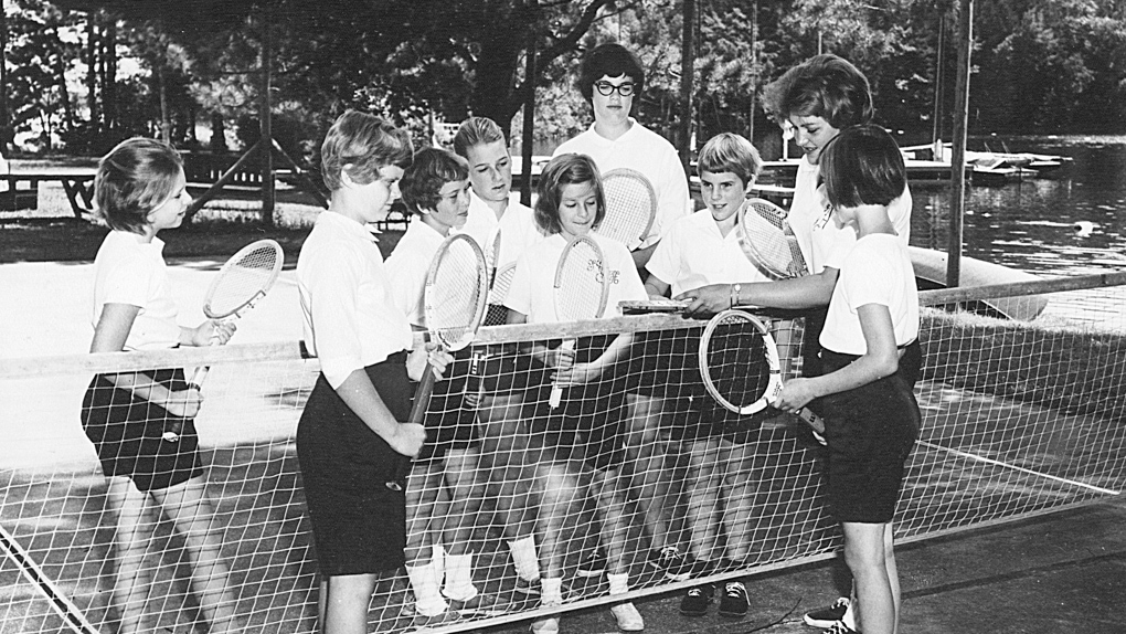 1962 photo of campers gathered around net on tennis court