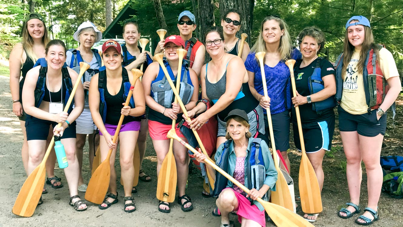 85th Alumni Reunion group holding canoe paddles
