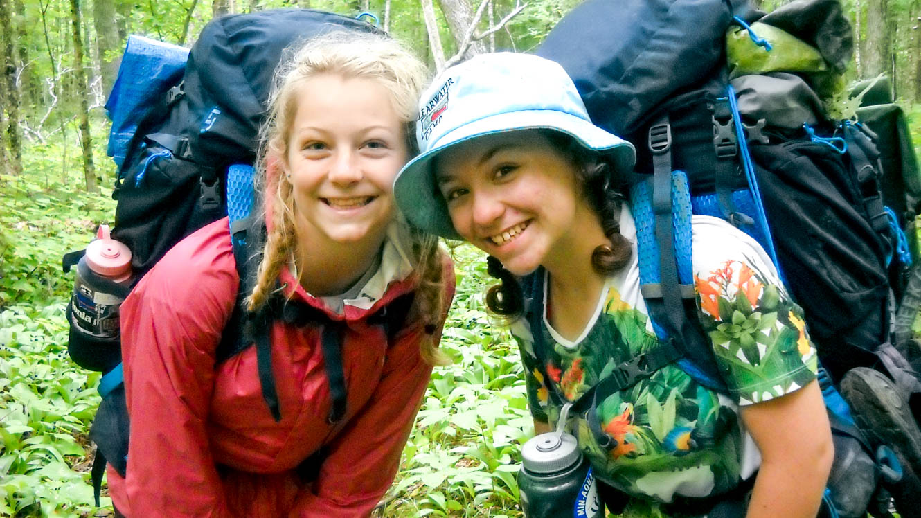 Girls smile at the camera on camp backpacking trip