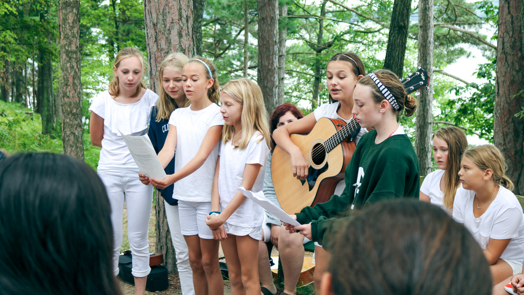 Campers perform song with guitar at Sunday Service