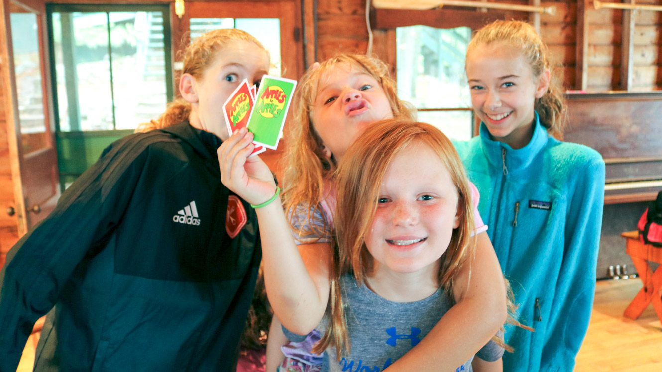 Group of campers makes silly faces with Apples to Apples cards