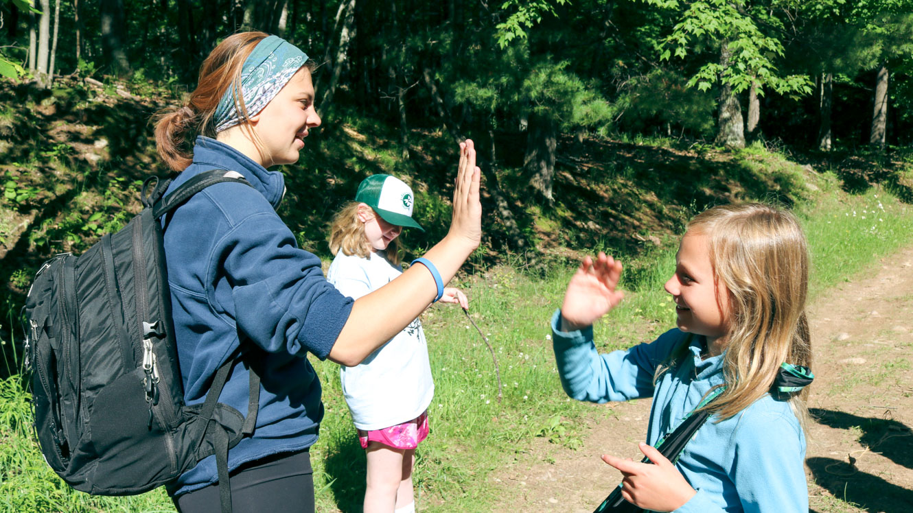 Camp staff member high fives young camper