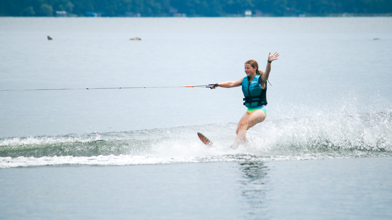 Girl waves while water skiing at summer camp