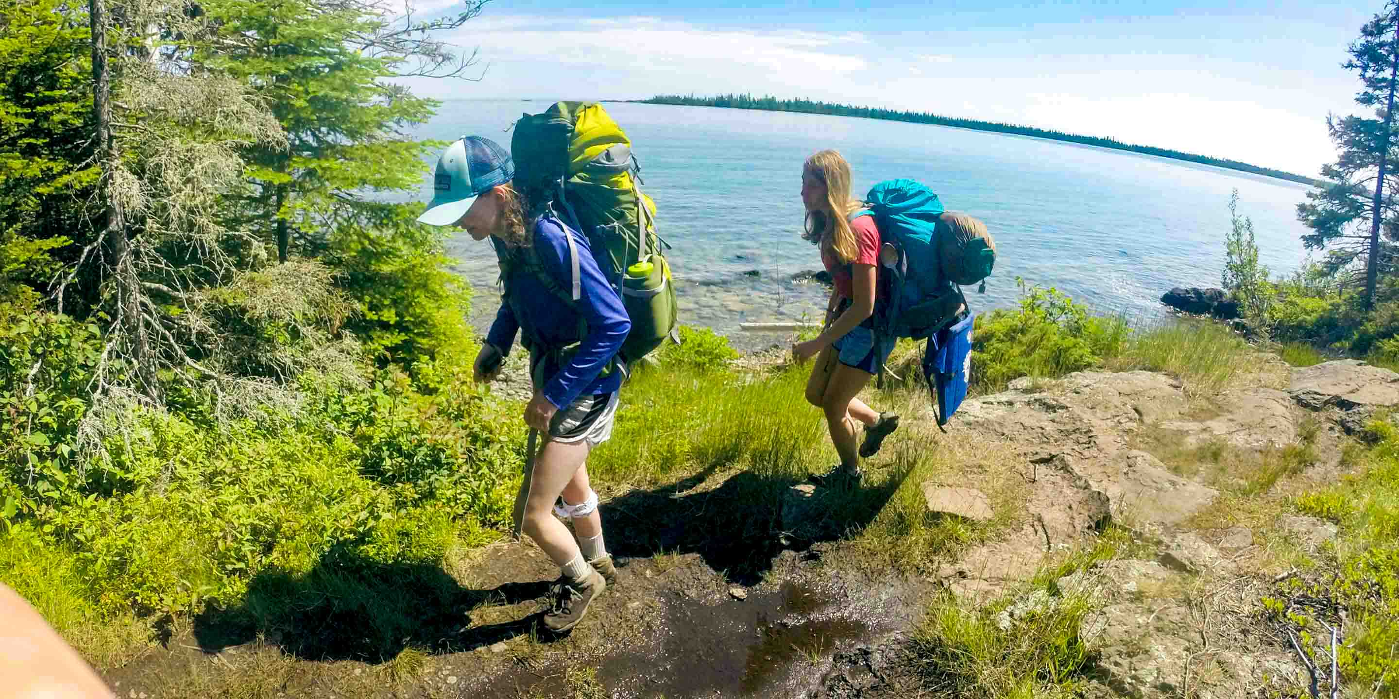 Girls backpack along lakeshore during camp trip
