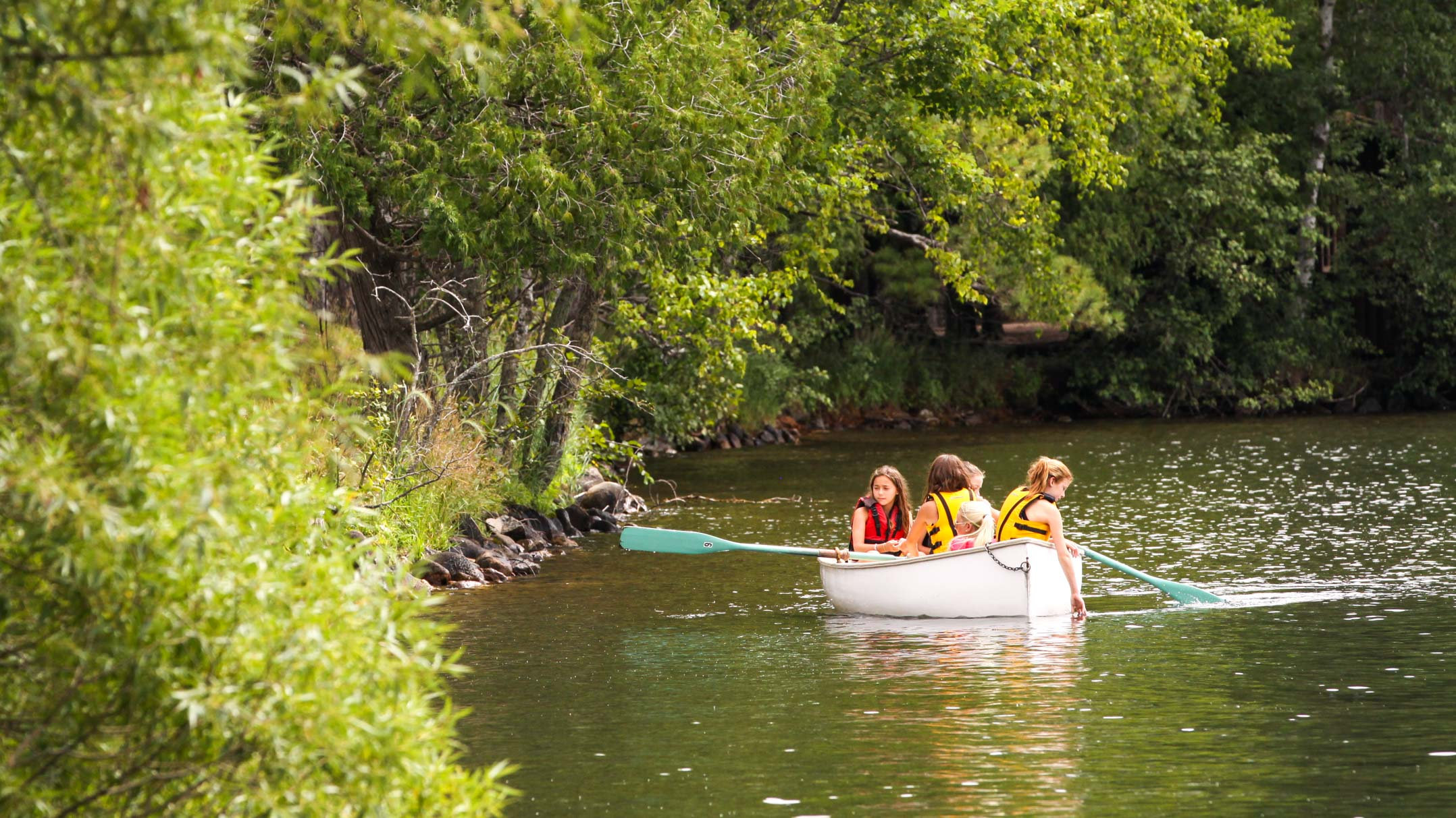 Campers paddle canoe along Clearwater shoreline