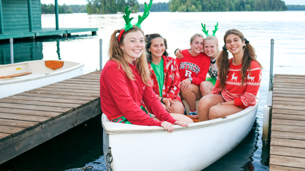Campers in Christmas garb sit in docked canoe