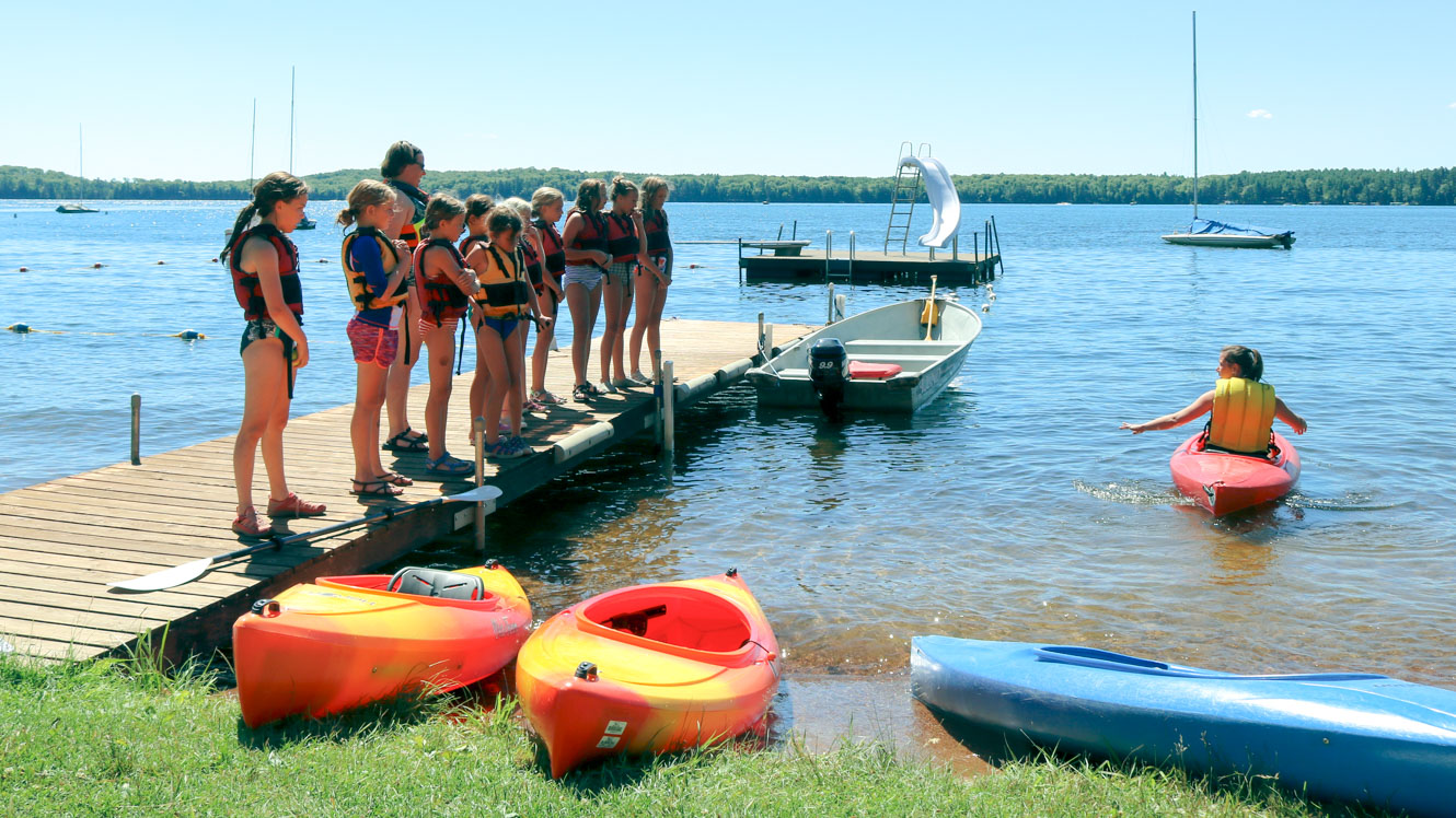 Campers line up on dock to learn kayak safety