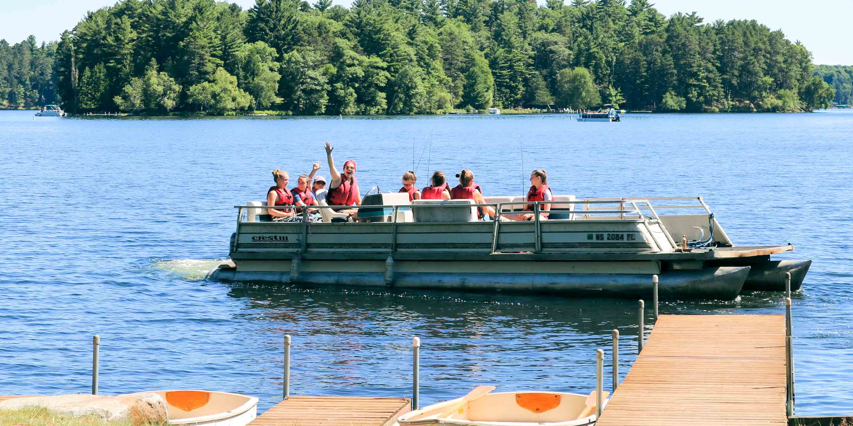 Group of campers waves from fishing boat