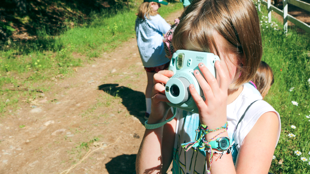 Young girl takes picture with turquoise camera