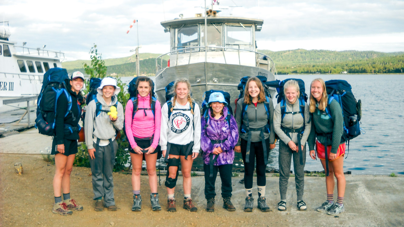 Group stands in front of boat on camp trip