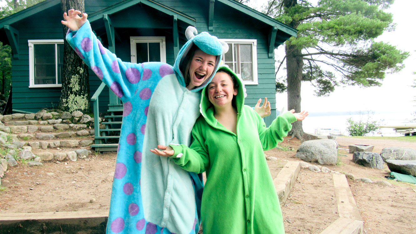 Young women look excited while wearing monster onesies