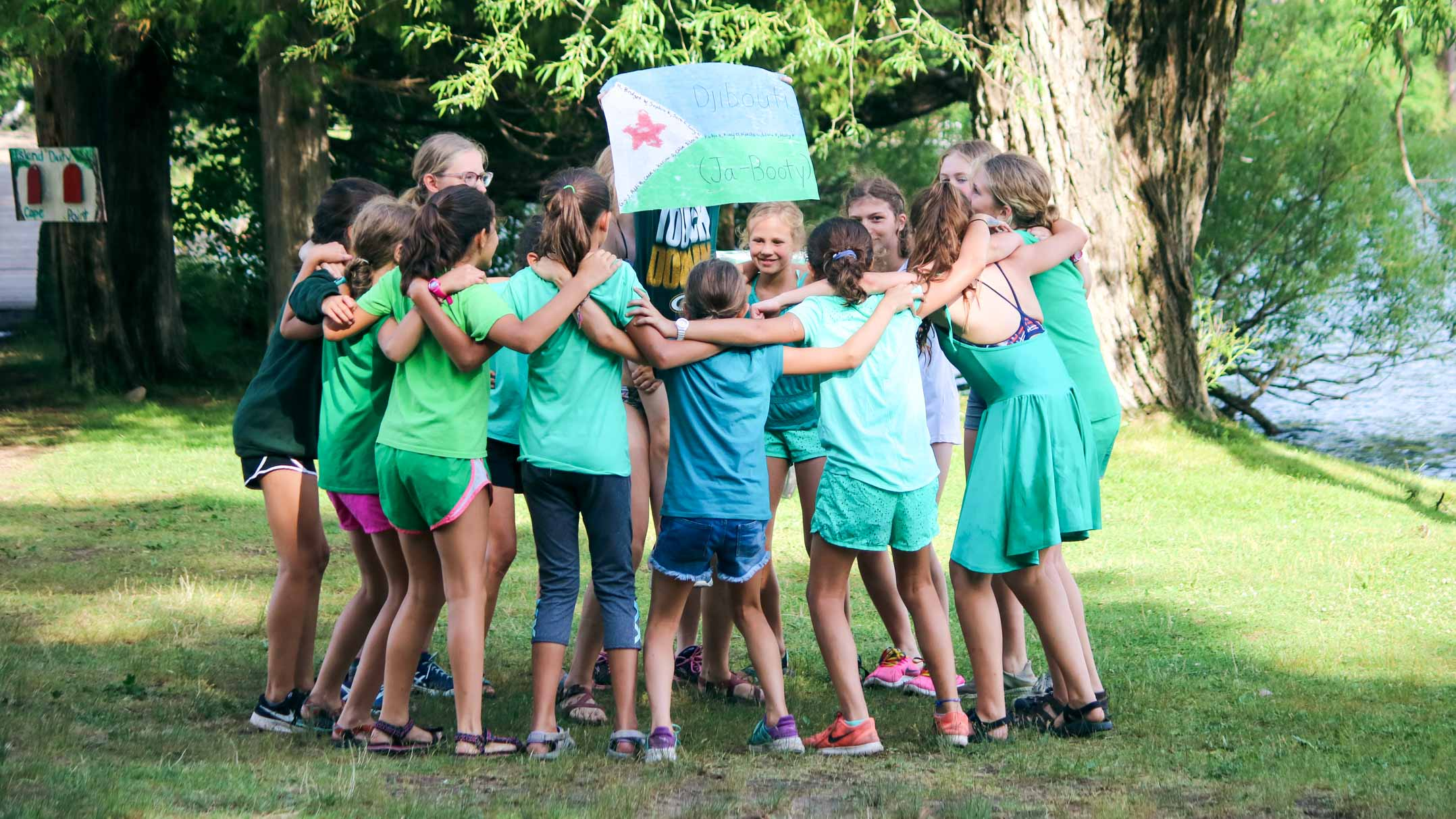 Group of campers circles up, holding camp Olympics Djibouti sign
