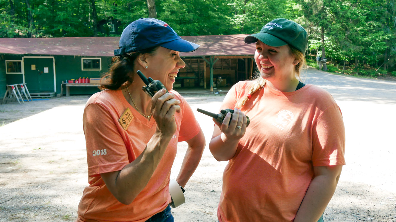 Camp staff laughing while holding walkie talkies