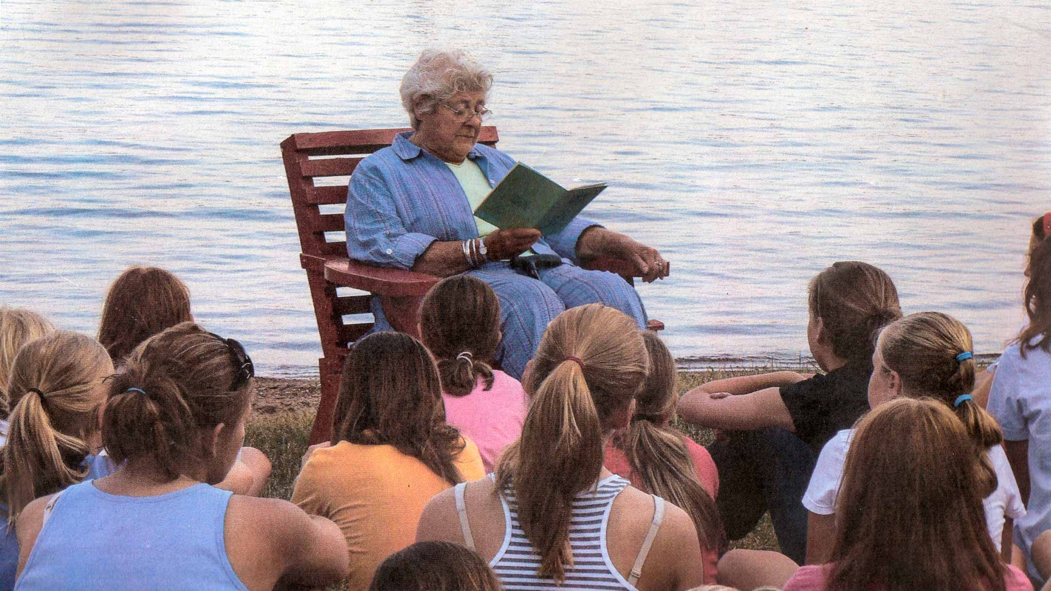 Sunny reads to campers by lakeshore