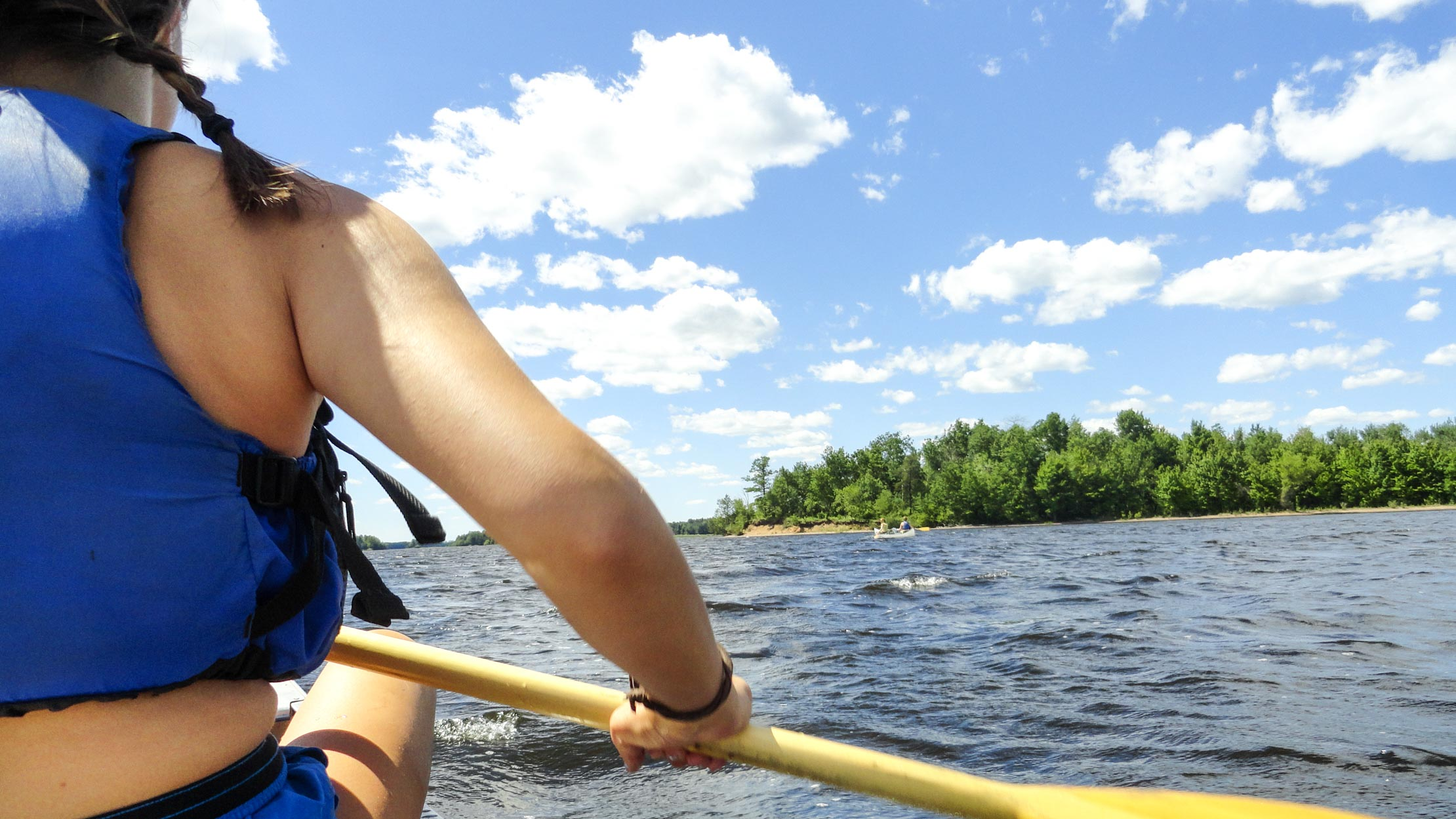 View of camper's back while paddling canoe