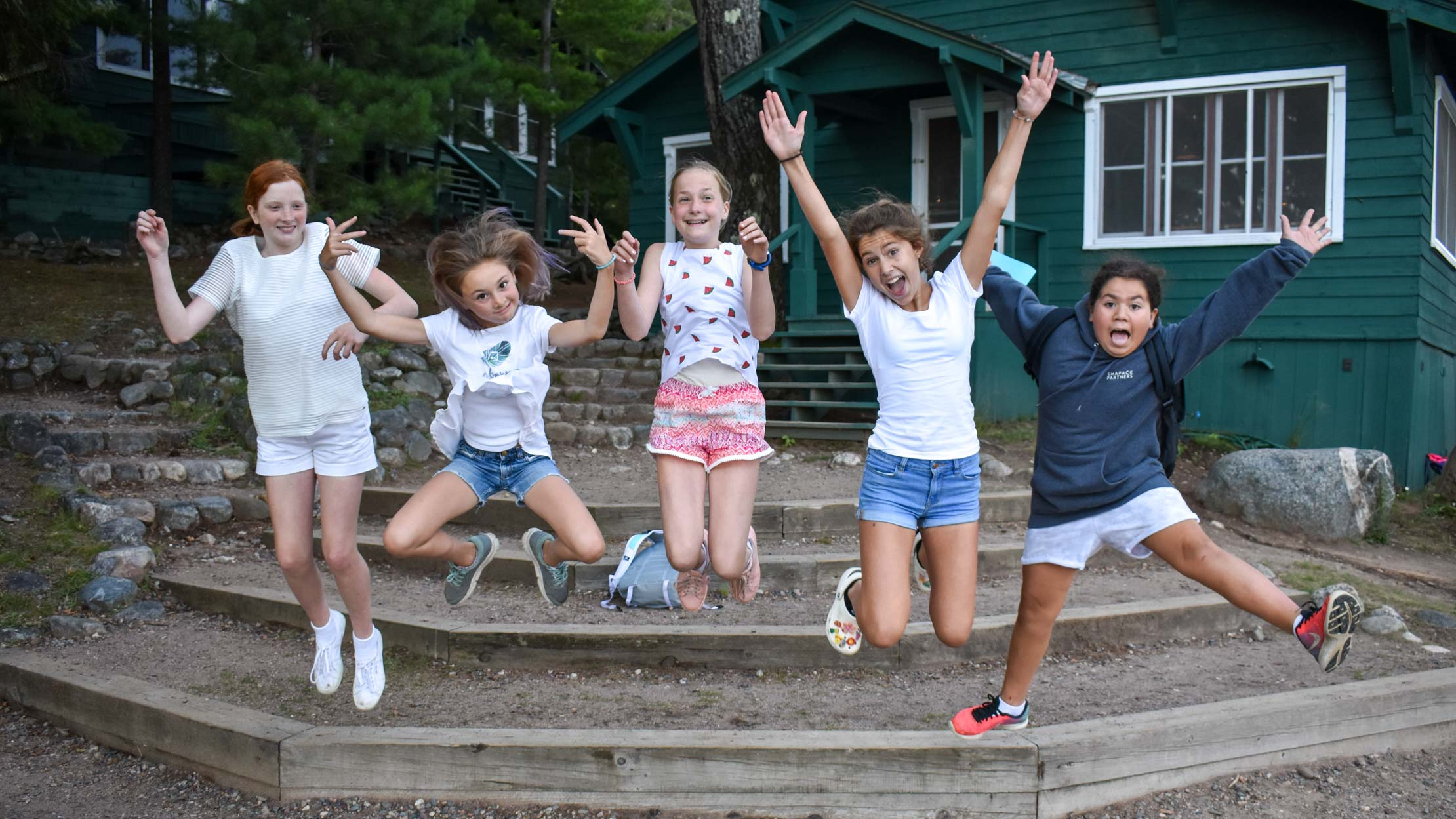 Group of campers jumping off steps