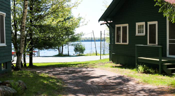 View of tennis court and lake past camp building