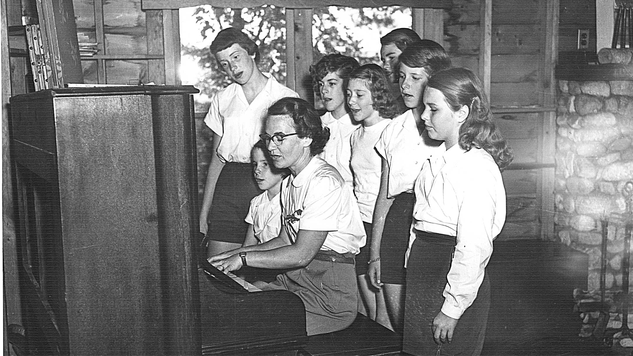 1951 photo of campers gathered around piano to sing