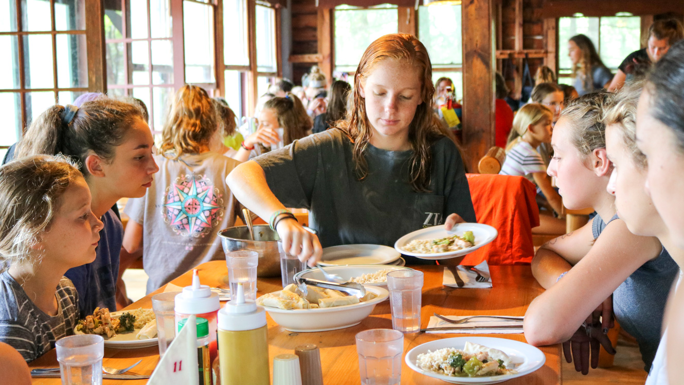 Camper serves food to others at table