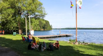 Campers sit in a circle near flagpole by lake