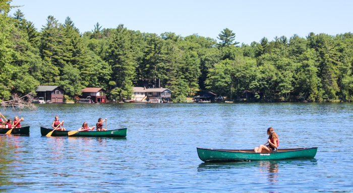 Campers canoe near shoreline with cabins behind them