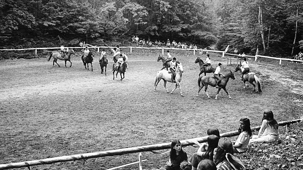 Black and white photo of campers horseback riding in 1978