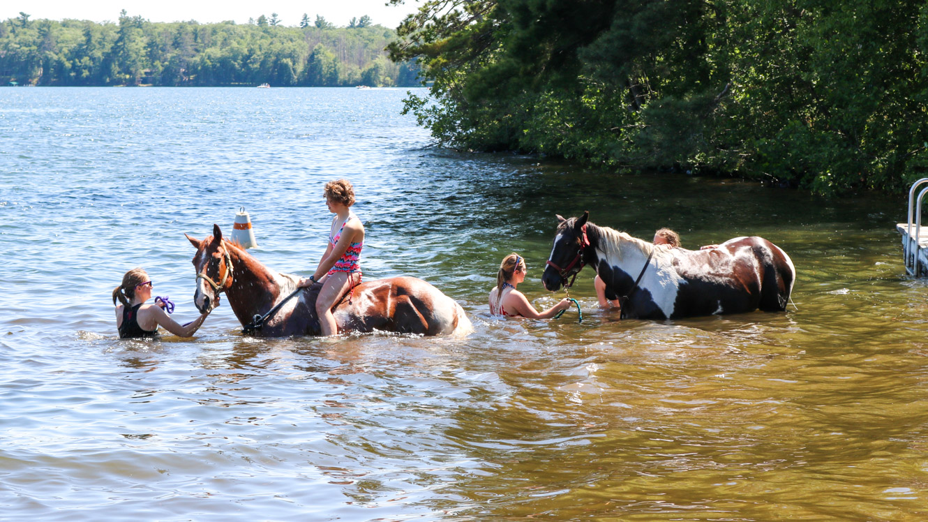 Campers ride horses into the water