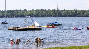 Campers swim in waterfront area in front of floating dock and boats