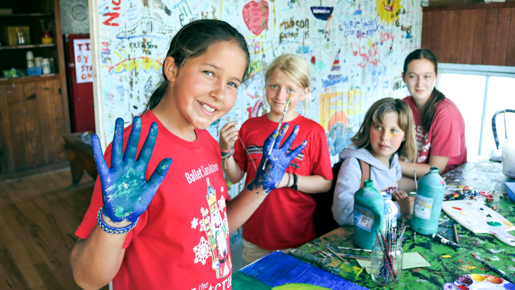 Camper holds up hands covered in blue paint