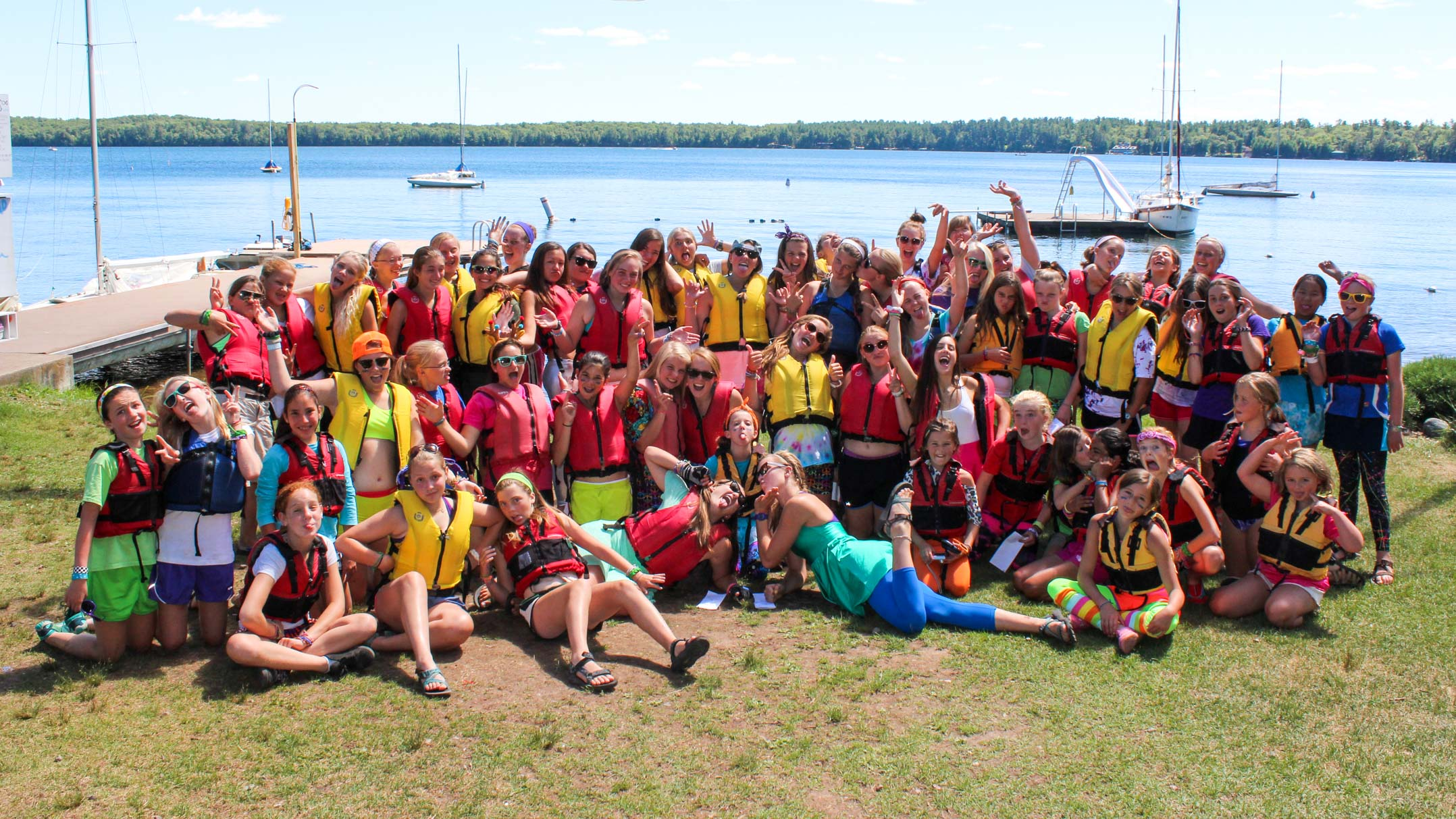 Group of campers pose in front of waterfront in life jackets