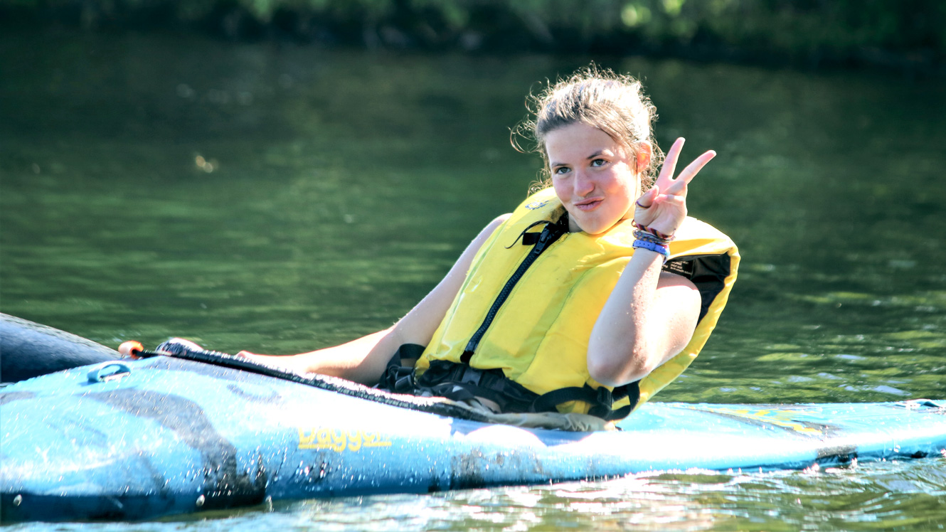 Camper gives peace sign while sitting in kayak