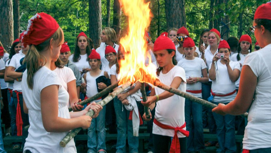 Campers hold torches together at Council Fire event