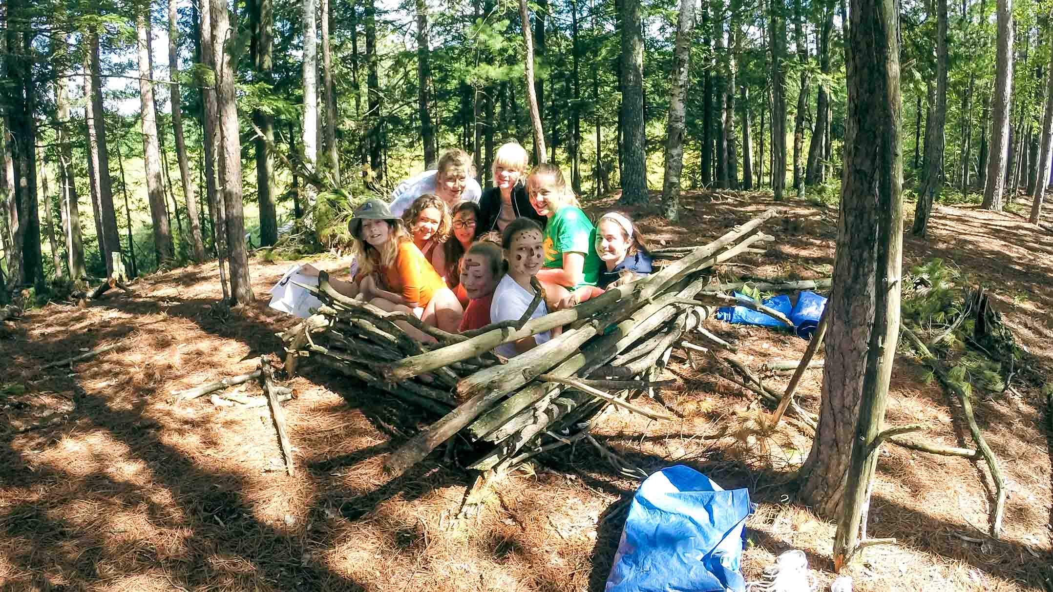 Group of campers sits in a square built of branches