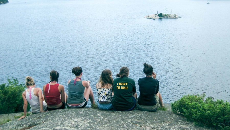Campers sit on rock and overlook lake