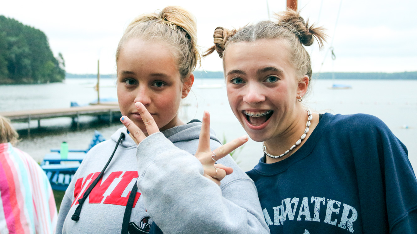 Two campers pose together with peace signs