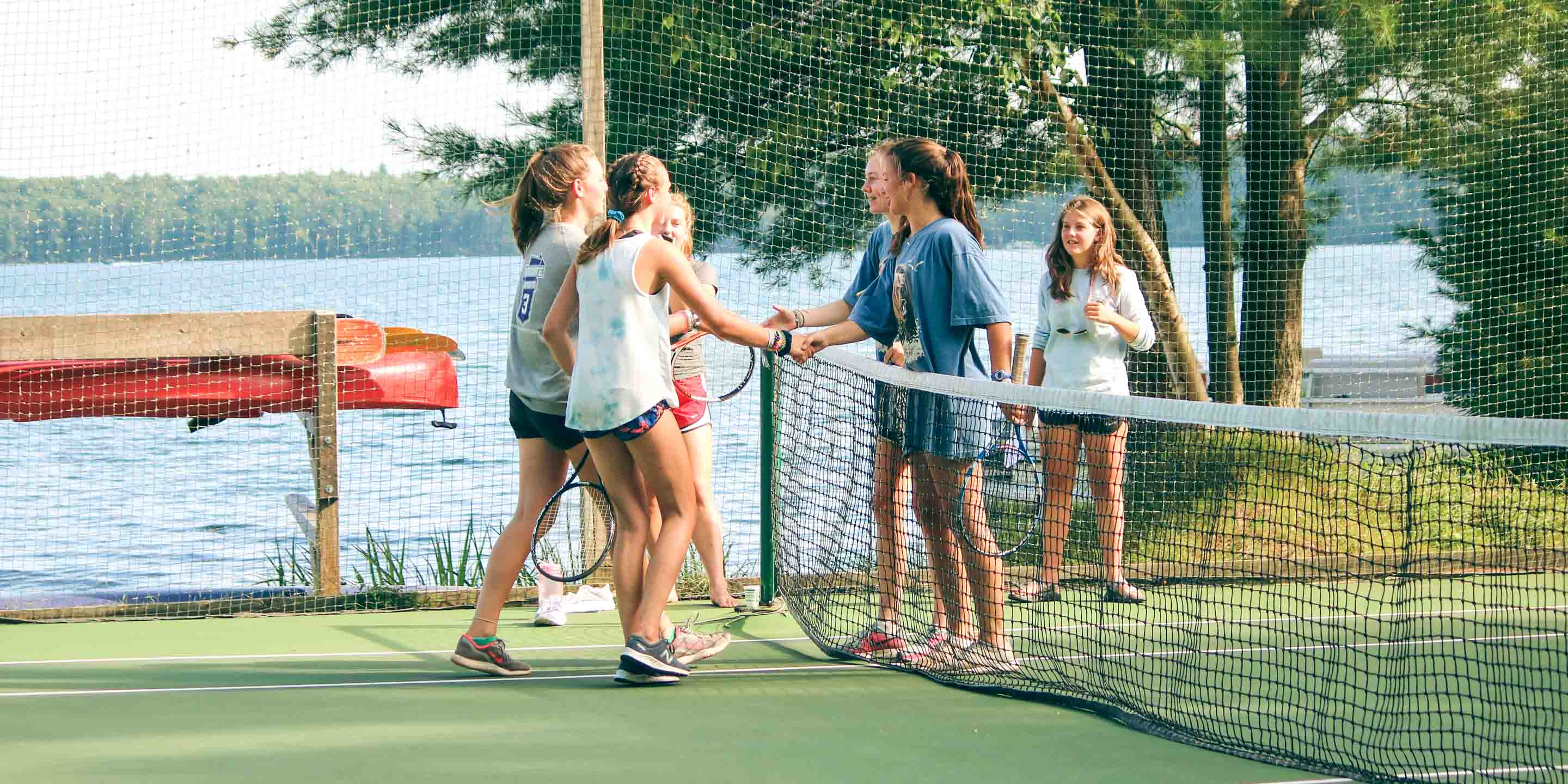 Campers shake hands after tennis match