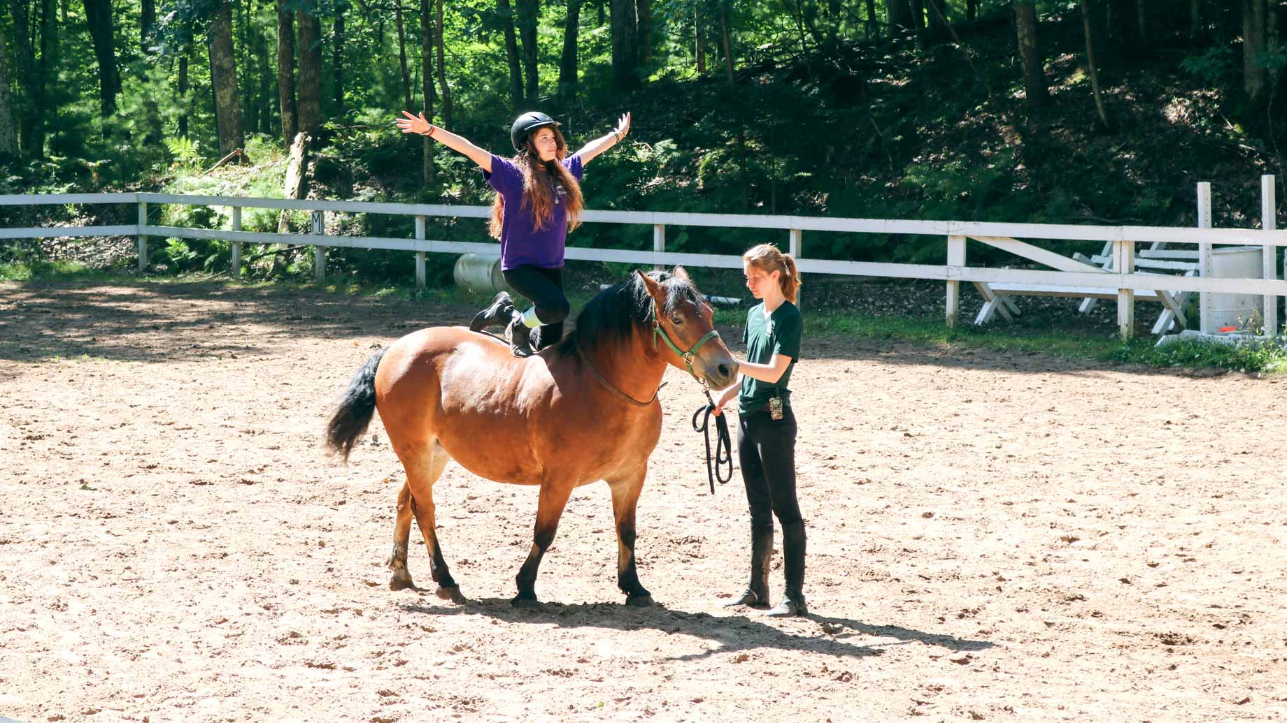 Girl kneels on back of horse with arms out