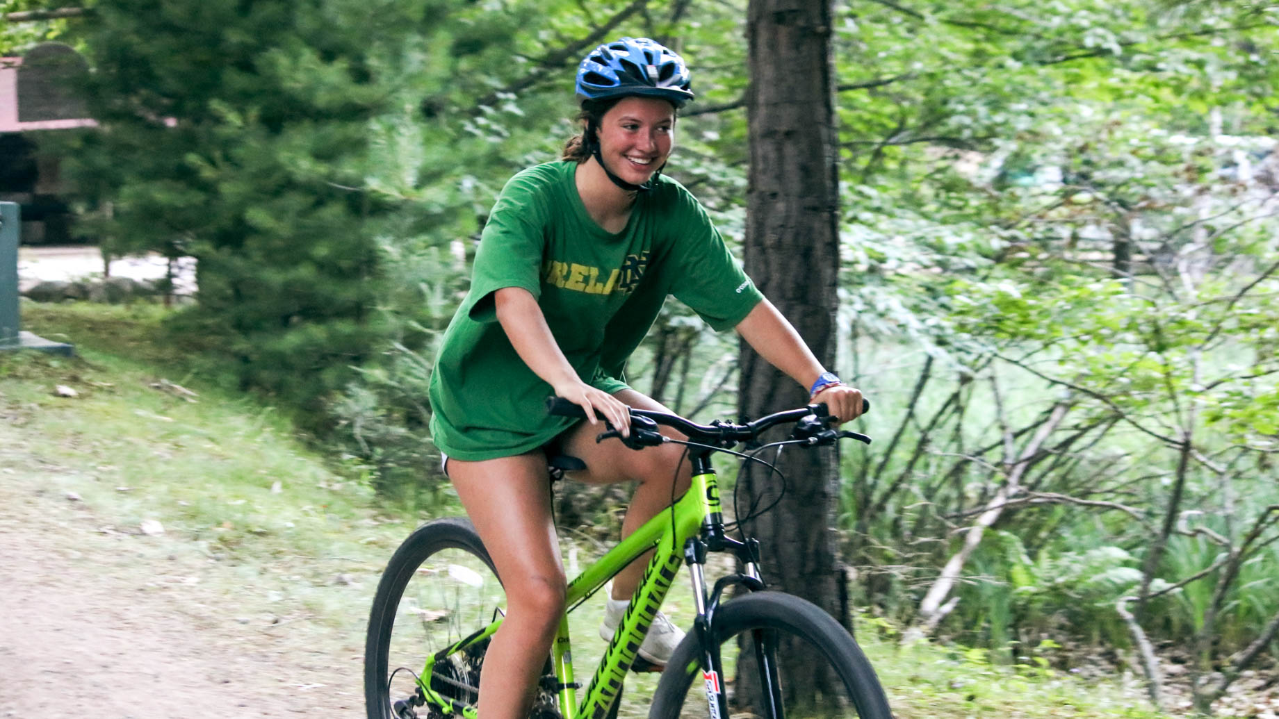 Girl rides mountain bike down summer camp path
