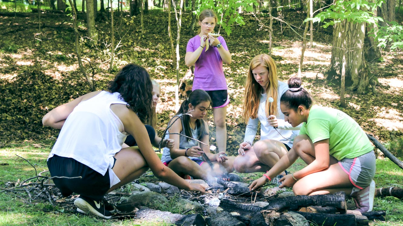 Group of campers cooks over outdoor fire